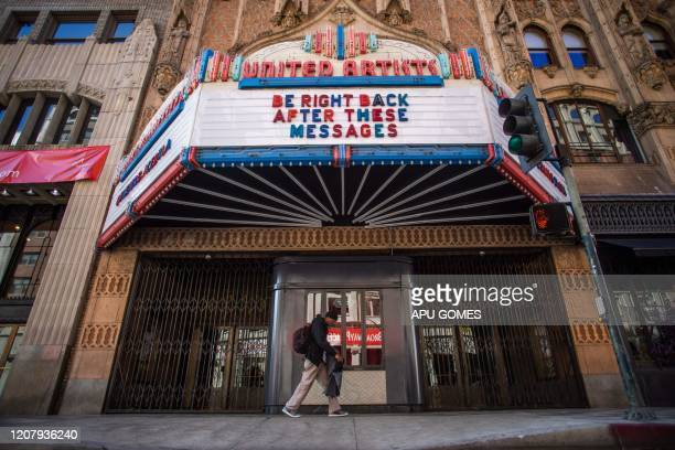 A man walks by a closed theater in Downtown Los Angeles on March 21 during the novel coronavirus outbreak All 40 million residents of California were...