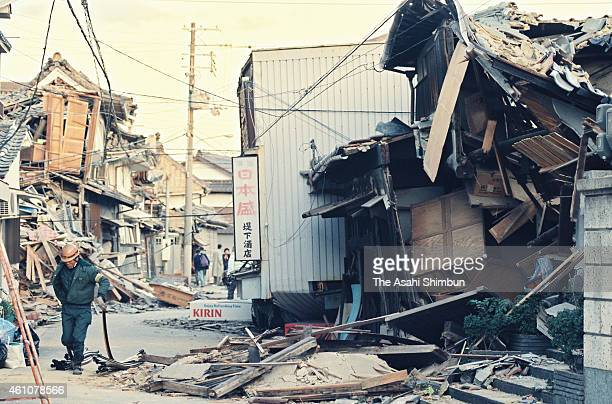 A man walks by a destroyed house after the strong earthquake on January 17 1995 in Nishinomiya Hyogo Japan Magnitude 73 strong earthquake jolted in...