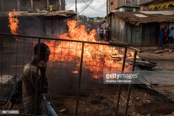 A man walks by a flaming roadblock with a bed frame looted from a house near by in the Kawangware slum on October 27 2017 in Nairobi Kenya Protests...