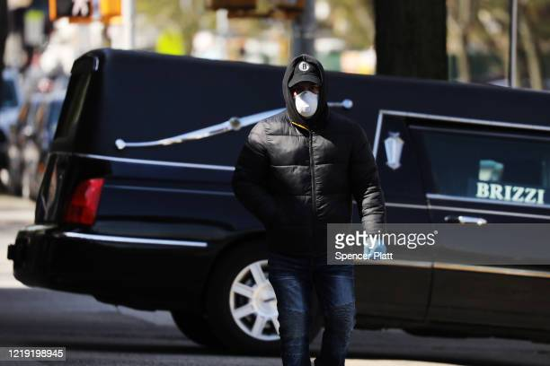 A man walks by a funeral home and hearse in the heavily Orthodox Borough Park neighborhood of Brooklyn which has scene a large number of deaths due...
