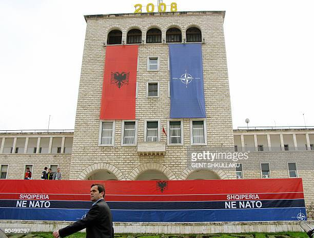 A man walks by a giant banner reading 'Albania in NATO' in Mother Teresa square in Tirana on April 3 2008 after Albania received the invitation to...
