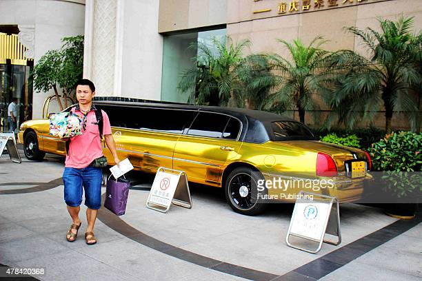 A man walks by a goldcoated 85meterlong stretched Lincoln limousine at a luxury hotel on June 25 2015 in Chongquing China The rent for the limo is...