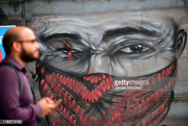 A man walks by a graffiti depicting a oneeyed demonstrator in clear reference to those injured in recent clashes with riotpolice in Santiago on...