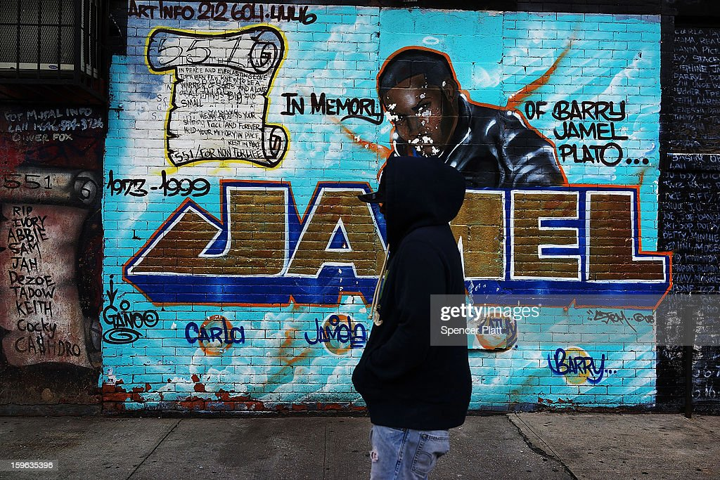 A man walks by a graffiti memorial on a wall in memory of an individual killed in the Bedford-Stuyvesant neighborhood on January 17, 2013 in the Brooklyn borough of New York City. Visual memorials honoring residents who in many cases met violent ends decorate many Brooklyn neighborhoods. New York Governor Andrew Cuomo recently signed into law the New York Secure Ammunition and Firearms Enforcement Act, one of the toughest gun laws in the country.
