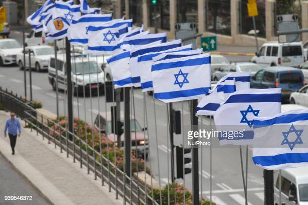 A man walks by a line of Israeli national flags near the walls of the Old Town in Jerusalem Wednesday 14 March 2018 in Jerusalem Israel