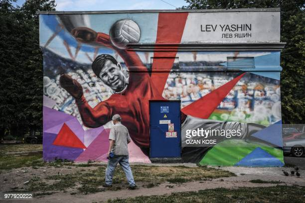A man walks by a mural depicting legendary Soviet goalkeeper Lev Yashin in Kaliningrad on June 18 2018 during the Russia 2018 FIFA World Cup football...