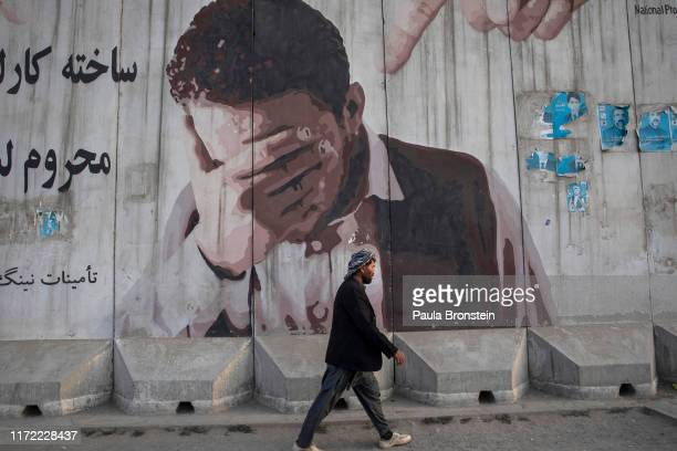Man walks by a mural painted on a blast wall on September 29, 2019 in Kabul, Afghanistan. The country's Interior Ministry said there had been 68...