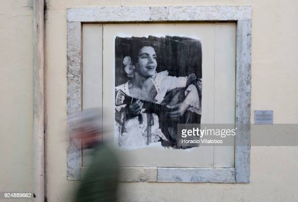 A man walks by a picture of Fado singer Amalia Rodrigues part of Retratos de Fado exhibit hanging in Mouraria neighborhood on February 24 2018 in...