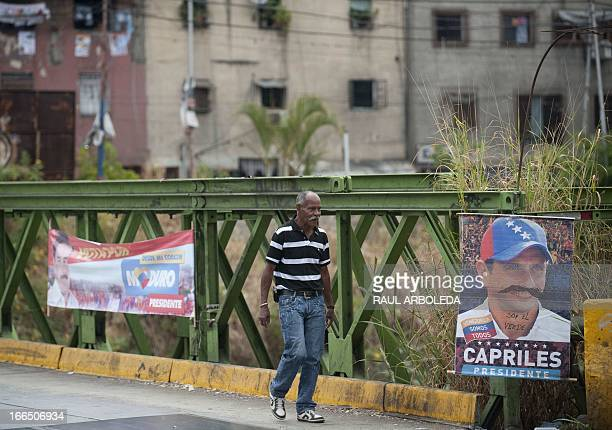 A man walks by a political propaganda poster with a picture of Venezuelan opposition presidential candidate Henrique Capriles with a painted mustache...
