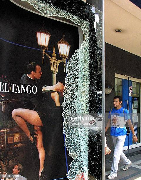Man walks by a poster behind broken glass at a damaged bank in Buenos Aires 21 December 2001 after 48 hours of riots rampaged through the city. At...