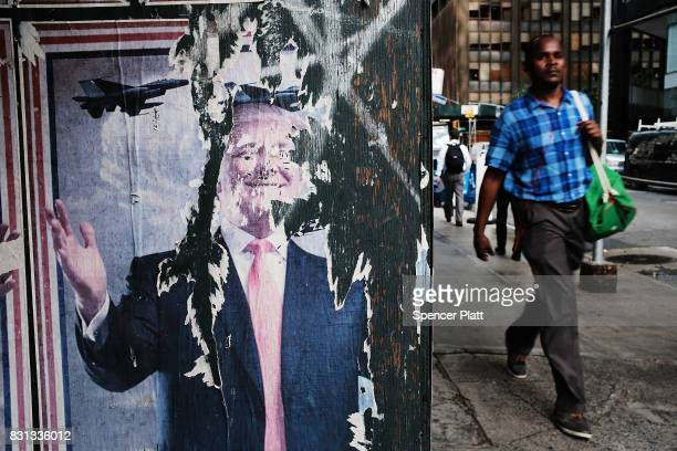 A man walks by a poster featuring President Donald Trump on August 14 2017 in New York City Security throughout the Manhattan is high today as...
