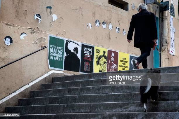 A man walks by a poster reading ' This year May 68 begins in April' in reference to the civil unrest in France during May 1968 in Paris on April 11...