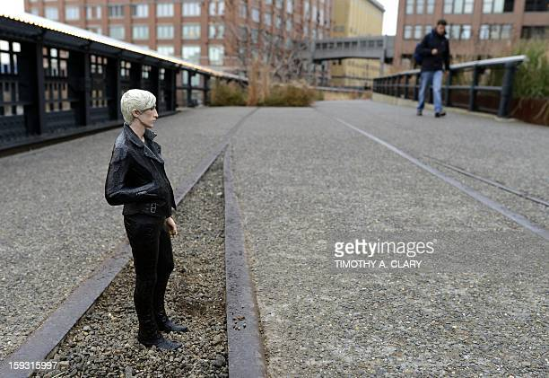 A man walks by a sculpture by Japanese artist Tomoaki Suzuki titled Carson a young man wearing a black leather jacket and tight pants on the High...