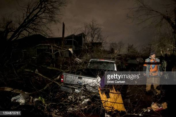 Man walks by a storm damaged pickup truck on Underwood St. On March 3, 2020 in Nashville, Tennessee. A tornado passed through Nashville just after...
