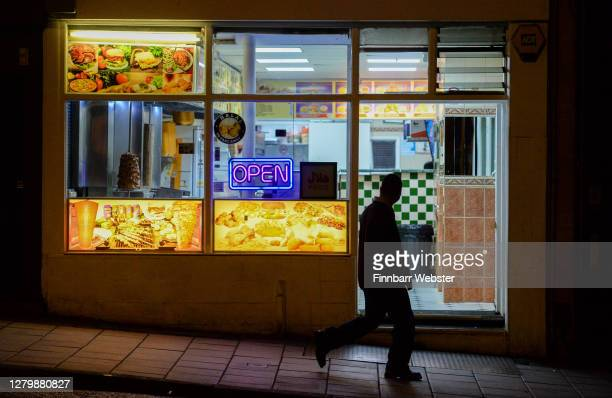 Man walks by a take-away on October 12, 2020 in Bristol, England. Despite the coronavirus infection rate in the city jumping from 44.2 new cases per...