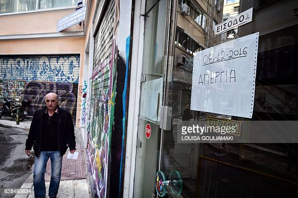 A man walks by a tax office in central Athens bearing sign 'strike' during a 24hours general strike on December 8 2016 Greece's leading unions...