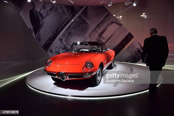 A man walks by a vintage Alfa Romeo 'Duetto' car during a presentation of the new Alfa Romeo car in the Alfa Romeo Museum renovated for the occasion...