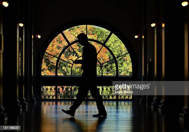 Man walks by a window looking out onto colorful leaves in the Russell Senate Office Building, on November 2, 2011 in Washington, DC. Fall foliage in...