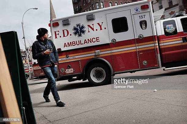 A man walks by ambulances near where three buildings collapsed and killed two men in the East Village last week on April 1 2015 in New York City The...