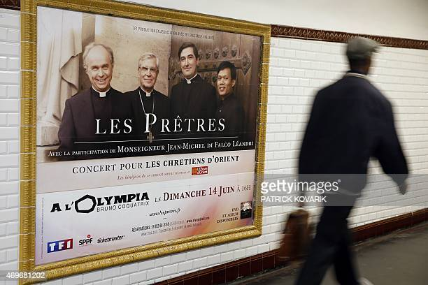 A man walks by an advertising poster for French music group 'The Priests' upcoming concert on April 14 2015 in Paris Frances RATP the company that...