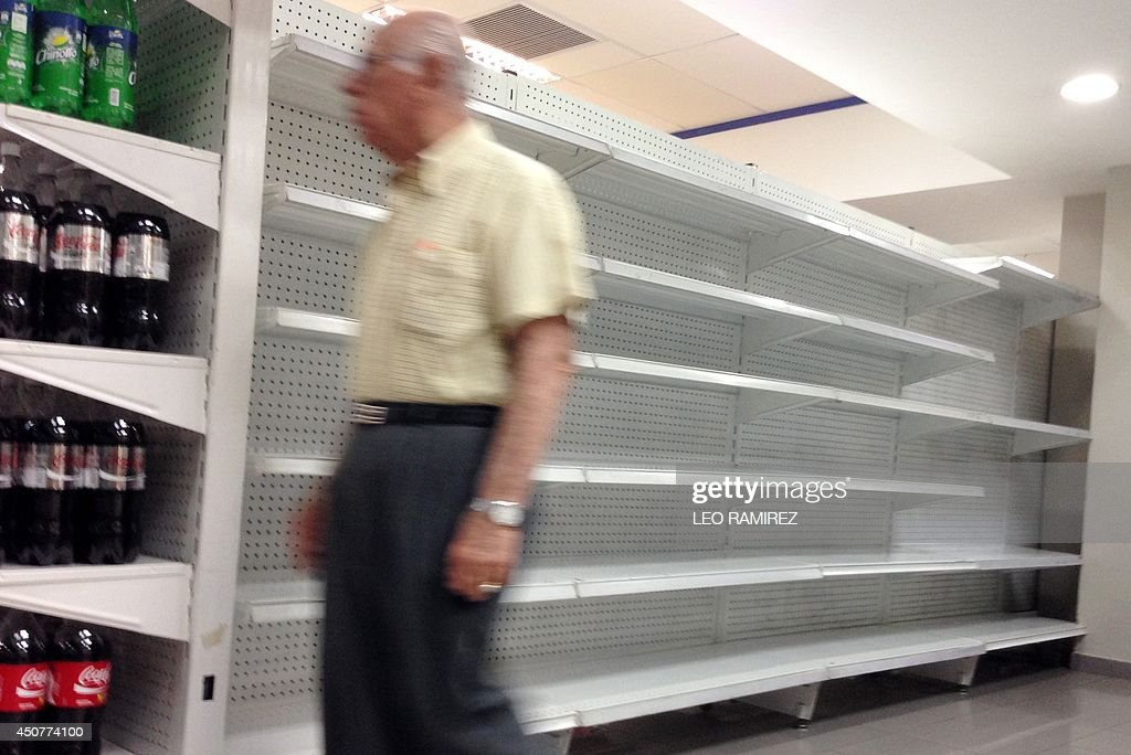 A man walks by an empty shelf inside a private market in Caracas on June 17, 2014. Acetone, hair colorants, deodorant, razors, makeup and even coffins are some of the big and small things of life and death, along with food and commodities in short supply in Venezuela.