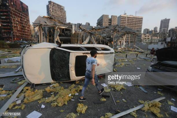 Man walks by an overturned car and destroyed buildings on August 4, 2020 in Beirut, Lebanon. At least 50 people were killed and thousands more...