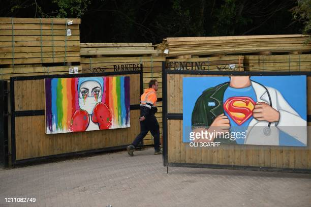 Man walks by artworks by artist Rachel List paying tribute to NHS staff battling the COVID-19 outbreak on the gates of a fencing company's premises...
