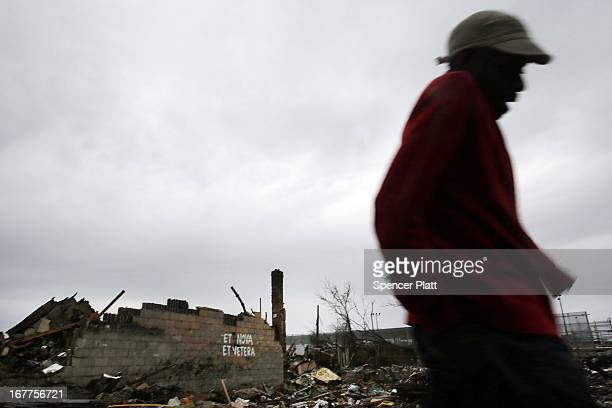 A man walks by destroyed buildings in the Rockaways which was heavily damaged in Hurricane Sandy on April 29 2013 in the Queens borough of New York...
