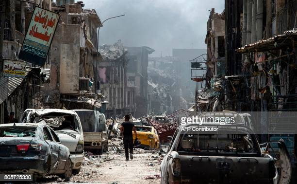 TOPSHOT A man walks by destroyed vehicles in a street in the Old City of Mosul on July 2 during the offensive to retake the city from Islamic State...