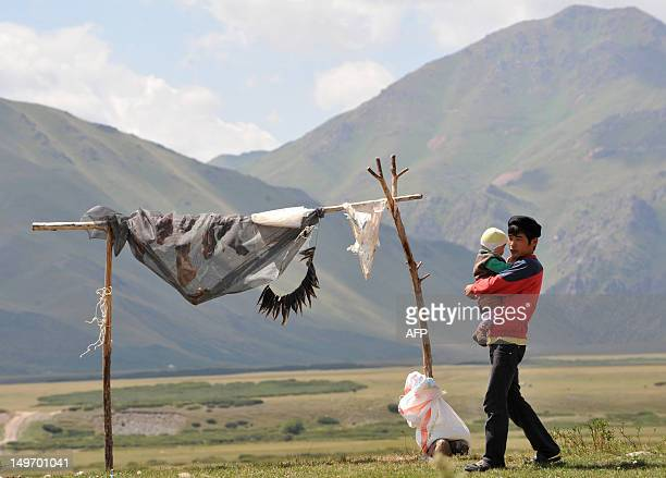 Man walks by drying meats in a settlement on the Suu-Samyr plateau 500 meters above the sea level, along the ancient Silk Road from Bishkek to Osh,...
