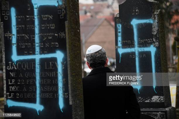 TOPSHOT A man walks by graves vandalised with swastikas at the Jewish cemetery in Quatzenheim on February 19 on the day of a nationwide marches...