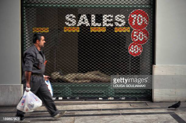 A man walks by one of hundreds shut down stores in the center of Athens on January 22 2013 Entering a sixth year straight of recession the heavily...
