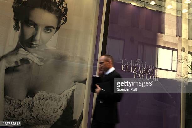 A man walks by pictures of Elizabeth Taylor at Christie's auction house where hundreds of items once belonging to the iconic actress have gone on the...