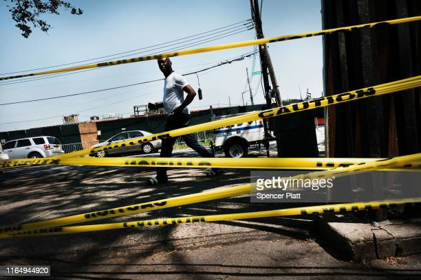 Man walks by police tape in the Brownsville neighborhood in Brooklyn where one person was shot and killed and 11 others were injured after two or...