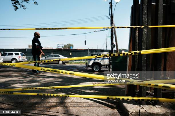 A man walks by police tape in the Brownsville neighborhood in Brooklyn where one person was shot and killed and 11 others were injured after two or...