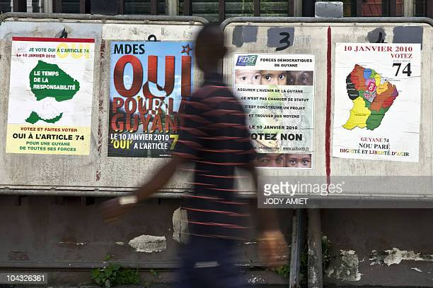 A man walks by political party billboards for the January 10 2010 referendum on the status and constitutional changes in the French South American...