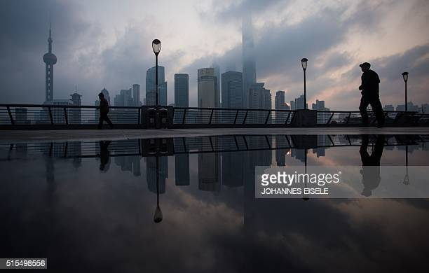 TOPSHOT A man walks by the Bund near the Huangpu river across the Pudong New Financial district in Shanghai on March 14 2016 China's leaders are...