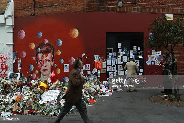 A man walks by the flowers letters and other items left on a mound continue to grow two weeks after the death of Brixton born English singer...