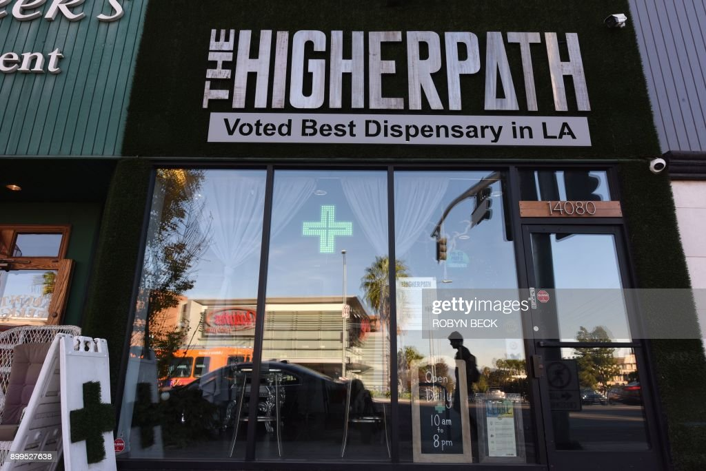 A man walks by the Higher Path medical marijuana dispensary in the Sherman Oaks area of Los Angeles, California, December 27, 2017. At the stroke of midnight on January 1, pot lovers in California may raise a joint, instead of a glass of champagne. America's wealthiest state is legalizing the growth, sale and consumption of recreational marijuana, opening the door to the world's biggest market. / AFP PHOTO / Robyn Beck