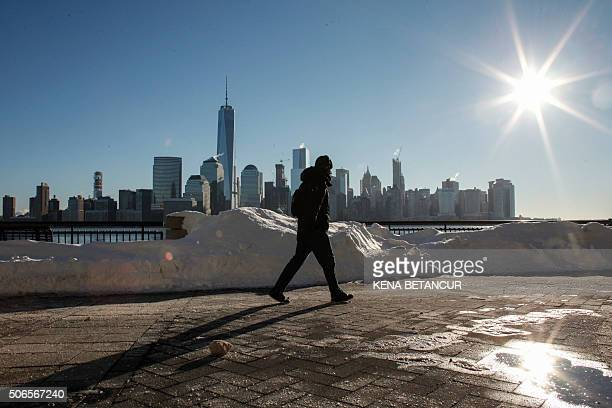 A man walks by the Hudson River Shore as the New York Skyline it's seen from Exchange Place on January 24 2016 in Jersey City A massive blizzard that...
