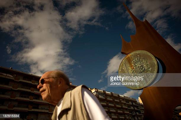 A man walks by the monument to the peseta the currency used in Spain before the euro on November 15 2011 in Fuengirola southern Spain AFP PHOTO /...