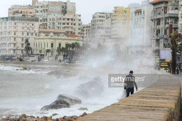 A man walks by the sea as the waves break against a coastal road during the annual winter storm in the Egyptian port city of Alexandria on January 19...