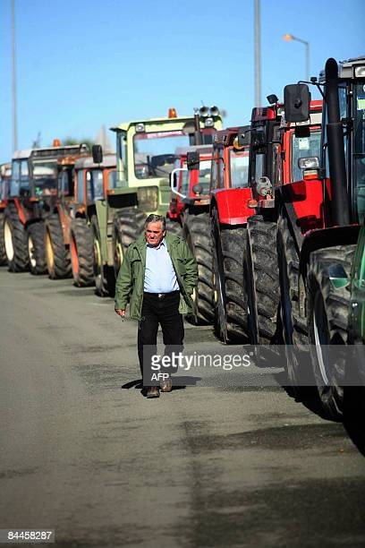 A man walks by tractors blocking the national AthensThessaloniki highway in Nikea near the city of Larisa central Greece on January 26 as they...