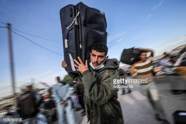 TOPSHOT A man walks carrying a suitcase as Palestinians wait to cross onto the Egyptian side through the Rafah border crossing between the Gaza Strip...