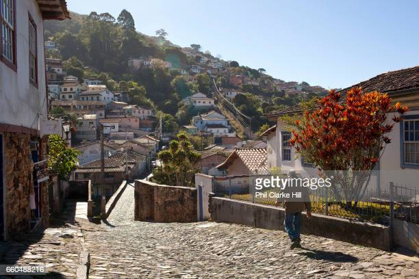 Man walks down a cobbled street. Colourful Colonial buildings in the city centre of Ouro Preto, in the state of Minas Gerais, Brazil. Ouro Preto,...