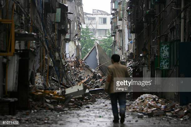 A man walks down a debris filled street after yesterday's earthquake May 13 2008 in Sichuan province Dujiangyan City China A major earthquake...