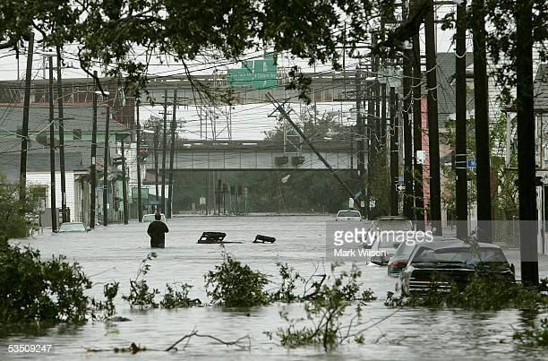A man walks down a flooded street after winds and rain from Hurricane Katrina hit the area August 29 2005 in New Orleans Louisiana Katrina was down...