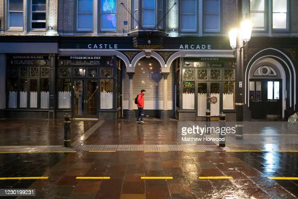 Man walks down a quiet High Street on December 18, 2020 in Cardiff, Wales. A two-household limit will be in place from December 23 to December 27 and...