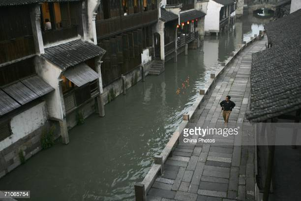 A man walks down a street along an ancient canal on May 26 2006 in Wuzhen Township of Tongxiang City Zhejiang Province China Wuzhen with a history of...