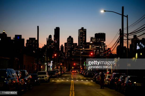 Man walks down a street in Queens with the skyline of Manhattan in the background on May 20, 2019 in New York City.